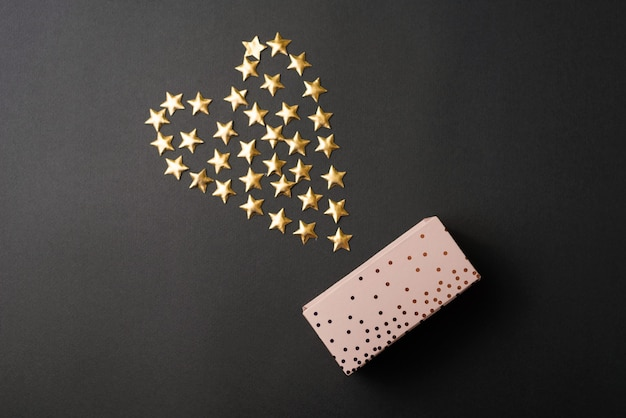 Coffret cadeau sur table sombre avec coeur fait d'étoiles