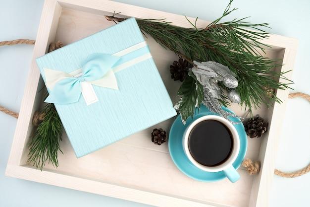 Coffret cadeau avec une tasse de café boules de noël et une branche d'épinette sur un plateau blanc