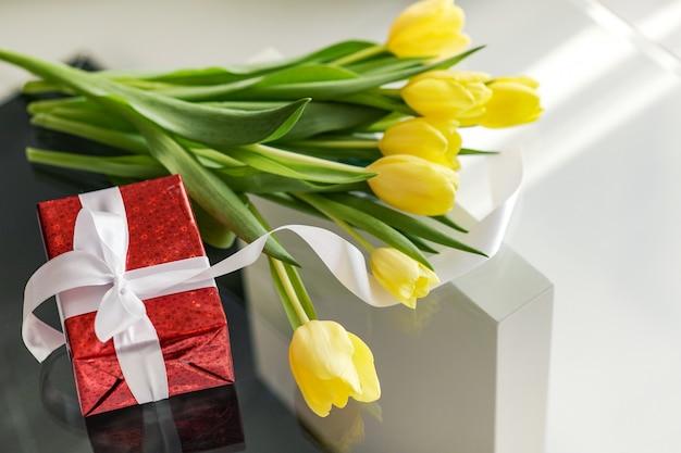 Coffret cadeau et tulipes jaunes se trouvent sur une table en verre