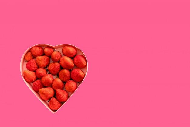 Coffret coeur rose avec des fraises pour la saint valentin sur fond rose.