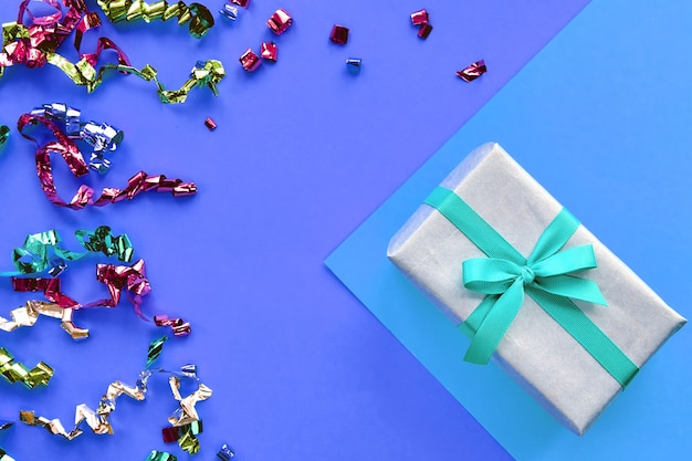 Coffret avec décorations ruban et confettis sur fond coloré de papier pastel. composition de noël ou de la saint-valentin avec espace de copie.