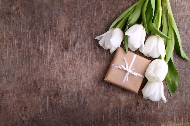 Coffret de fleurs (tulipes blanches) sur fond de bois rustique