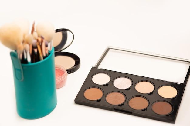 Coffret maquillage : kit pinceaux en étui, palette teint et poudre compacte sur fond gris