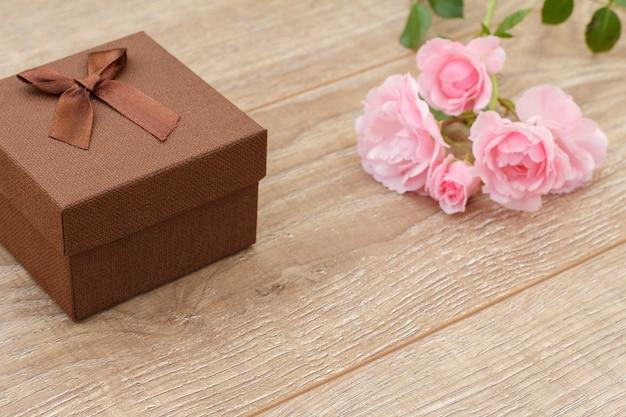 Coffret marron avec de belles roses en arrière-plan. concept de donner un cadeau en vacances. vue de dessus.