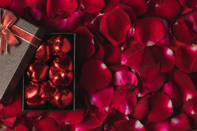 Coffret marron placé sur des pétales de rose rouges vue de dessus, thème de la saint-valentin