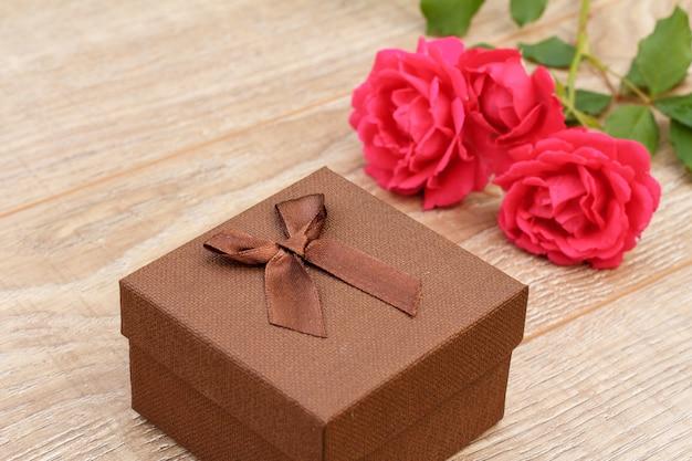 Coffret marron avec des roses rouges sur le fond en bois. concept de donner un cadeau en vacances. vue de dessus.