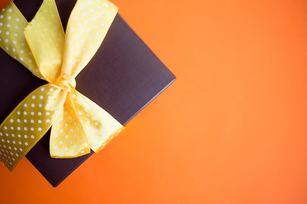 Coffret marron avec ruban jaune sur fond orange. vue de dessus avec espace de copie.