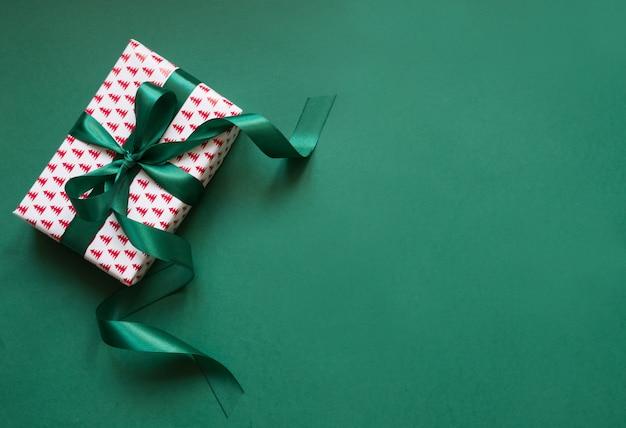 Coffret de noël avec ruban vert sur une surface verte. carte de vacances.
