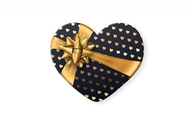Coffret noir en forme de coeur avec un arc doré isolé sur fond blanc