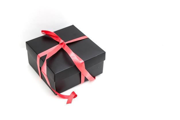 Coffret noir avec noeud de ruban rouge, sur fond blanc.