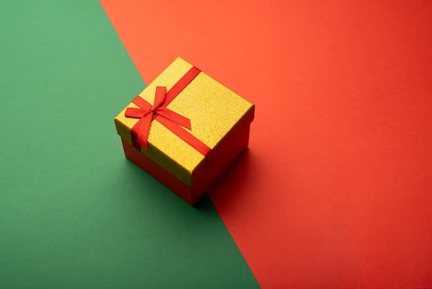 Coffret or avec ruban rouge sur fond vert et rouge vif