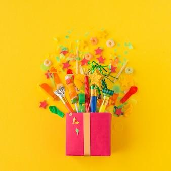 Coffret ouvert avec des bonbons et des accessoires de fête sur fond jaune