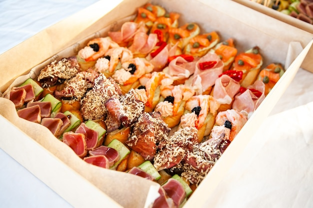 Coffret avec petits sandwichs, bruschetta avec charcuterie, fromage et fruits de mer pour buffet traiteur et fête.