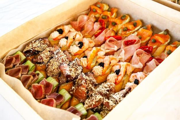 Coffret avec petits sandwichs, bruschetta avec charcuterie, fromage et fruits de mer. snack gastronomique dans une boîte en carton pour buffet traiteur pour fête.