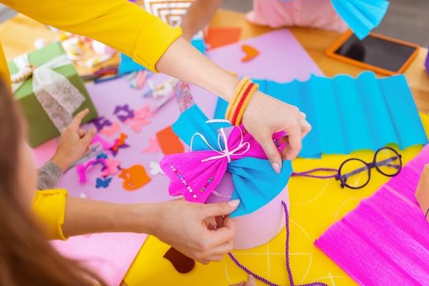 Coffret présent. vue de dessus d'un enseignant portant des bracelets décorant une boîte présente le montrant aux élèves