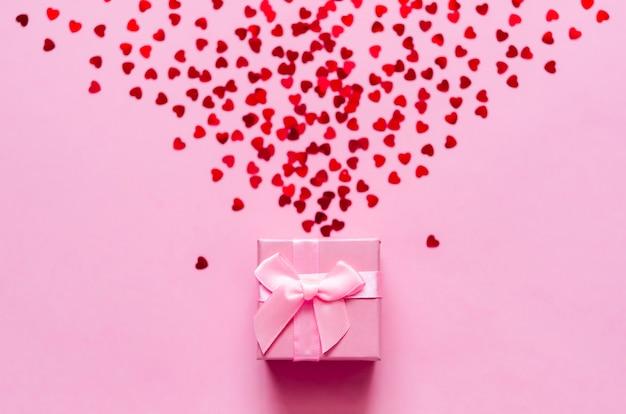 Coffret rose avec des coeurs rouges holographiques sur fond pastel. toile de fond festive. vue de dessus.