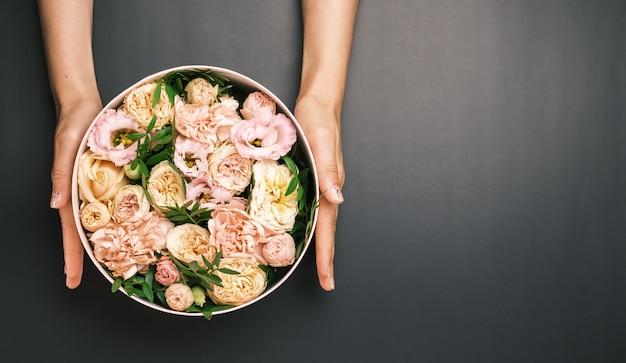 Coffret rose avec une composition florale dans les mains de la femme sur le fond noir avec espace copie