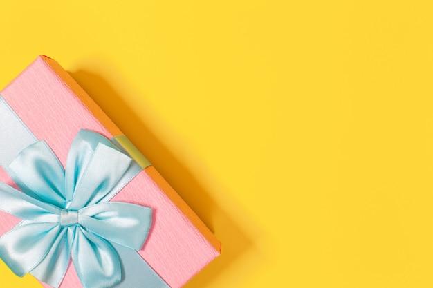 Coffret rose noué avec un ruban bleu avec un noeud en haut sur fond jaune. espace de copie.