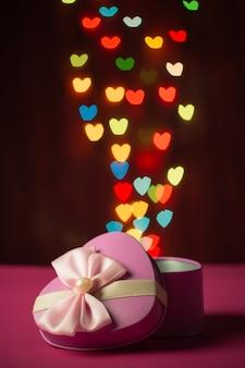 Coffret rose ouvert en forme de coeur avec bokeh défocalisé lumières colorées en forme de coeur fond