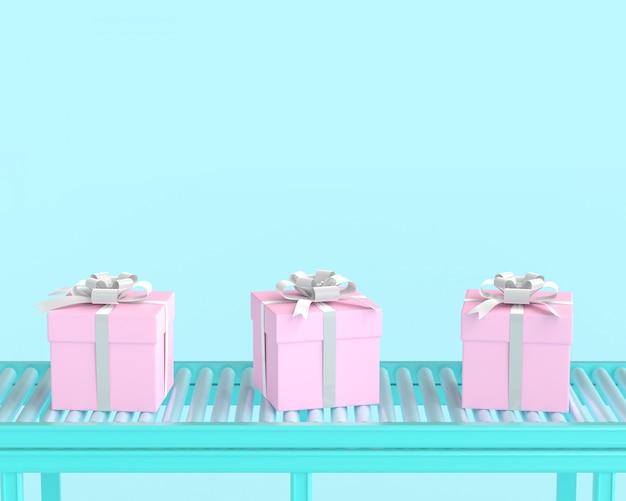 Coffret rose sur rouleau de convoyeur et fond de couleur pastel bleu.