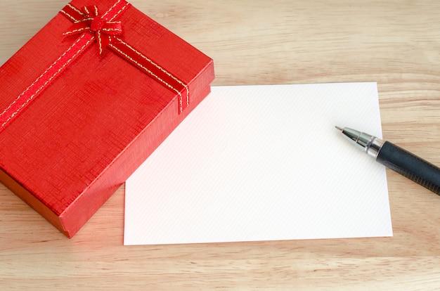 Coffret rouge avec carte vierge et stylo sur table en bois