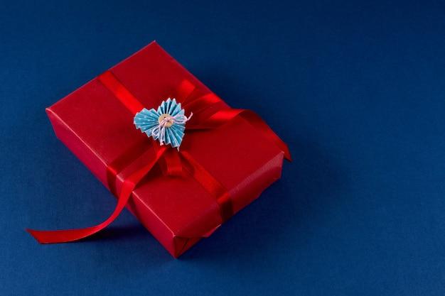 Coffret rouge avec coeur et noeud sur fond de couleur bleu classique 2020. concept d'emballage de la saint-valentin 14 février. mise à plat, espace de copie, vue de dessus.