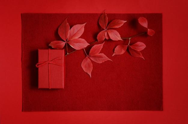 Coffret rouge sur fond rouge. cadeau romantique pour la saint valentin. vue de dessus avec place pour le texte. mise à plat, feuilles d'automne