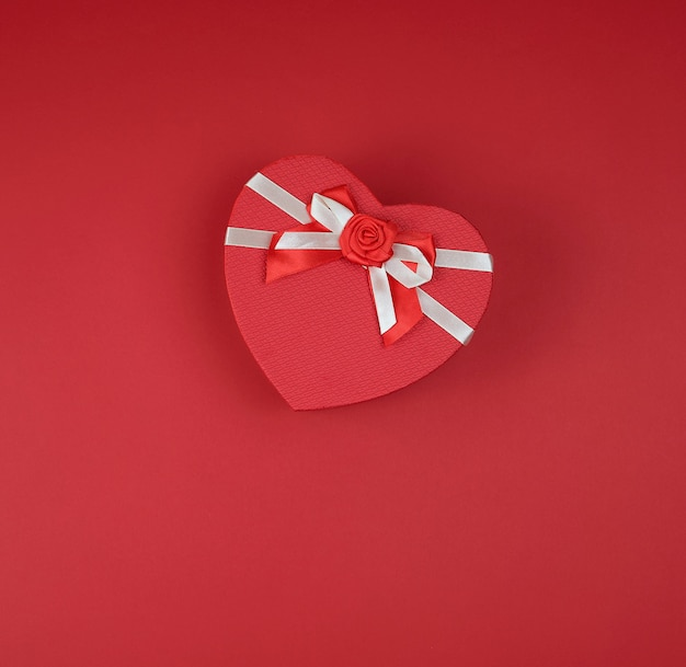 Coffret rouge en forme de coeur avec un arc