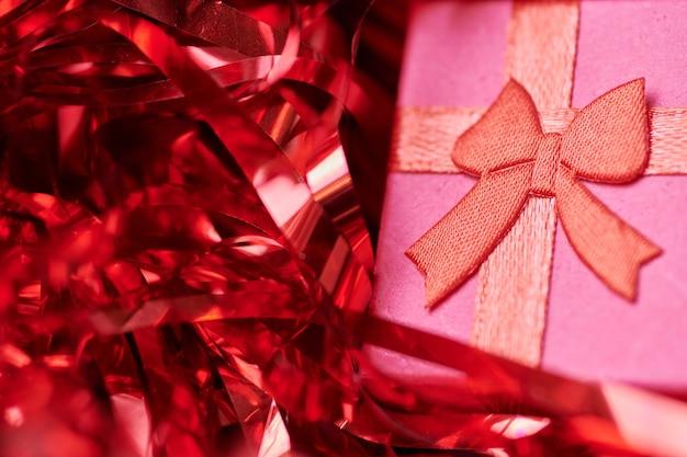 Coffret rouge en guirlande festive. petite boite fermée avec noeud et cadeau pour anniversaire ou mariage. coffret surprise pour un être cher.