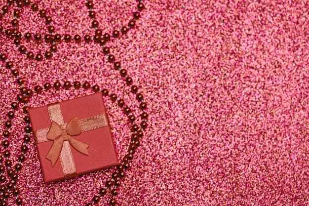 Coffret rouge sur paillettes festives, espace de copie. petite boite fermée avec noeud et cadeau pour anniversaire ou mariage. coffret surprise pour un être cher.