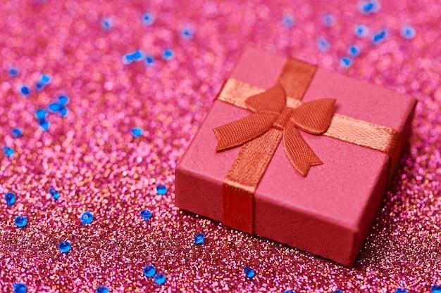 Coffret rouge sur paillettes festives. petite boite fermée avec noeud et cadeau pour anniversaire ou mariage. coffret surprise pour un être cher.