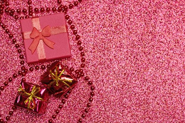 Coffret rouge sur paillettes festives. petite boite fermée avec noeud et cadeau pour anniversaire ou mariage