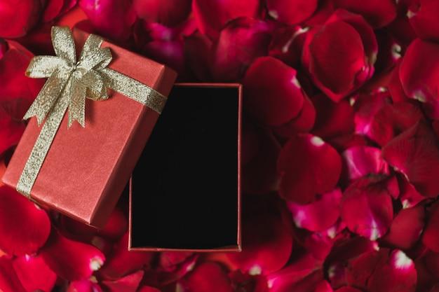 Coffret rouge placé sur des pétales de rose rouges vue de dessus, thème de la saint-valentin