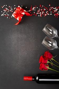 Coffret saint valentin et bouteille de vin sur fond de pierre avec espace copie pour vos salutations. vue de dessus à plat
