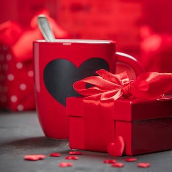 Coffret saint valentin tasses rouges et roses sur un fond en bois.