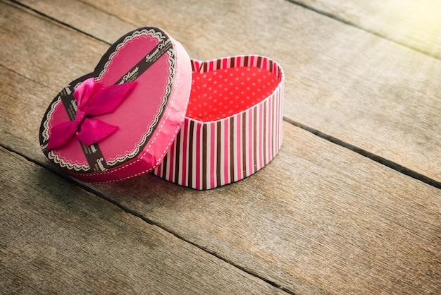 Coffret saint valentin sur de vieilles plaques en bois vintage en forme de coeur.