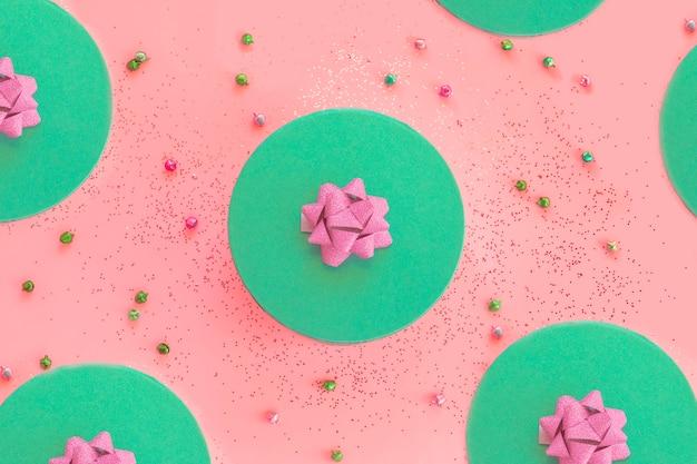 Coffret vert biscay rond avec motif de composition ouverte de ruban rose avec des grelots et des paillettes sur fond rose