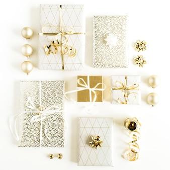 Coffrets cadeaux avec des arcs et des décorations en or sur une surface blanche. nouvel an, plat de fête de noël, vue du dessus