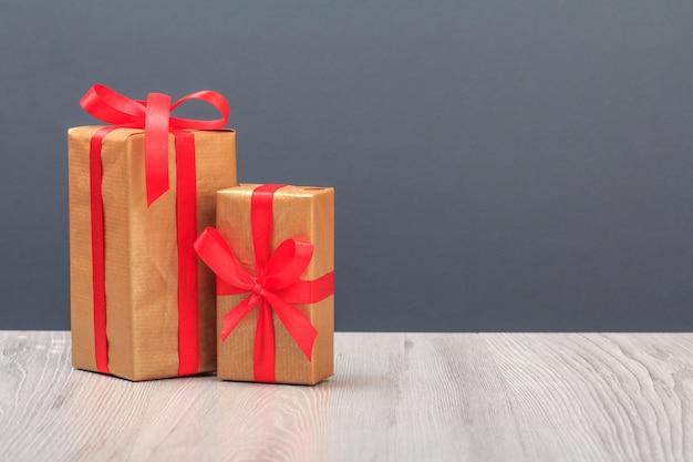 Coffrets cadeaux attachés avec des rubans rouges sur des planches en bois et fond gris. concept de jour de célébration.