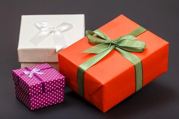 Coffrets cadeaux attachés avec des rubans verts, rouges et blancs sur fond noir. concept de jour de célébration.