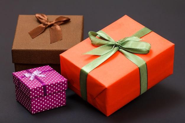 Coffrets cadeaux attachés avec des rubans verts, rouges et marrons sur fond noir. concept de jour de célébration.