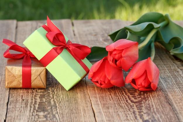 Coffrets cadeaux avec de belles tulipes sur les planches de bois. concept de donner un cadeau en vacances. vue de dessus.