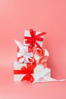 Coffrets cadeaux blancs avec des rubans de satin rouges sur fond rose. cadeaux festifs pour la saint-valentin, la journée internationale de la femme, le mariage ou les fiançailles.
