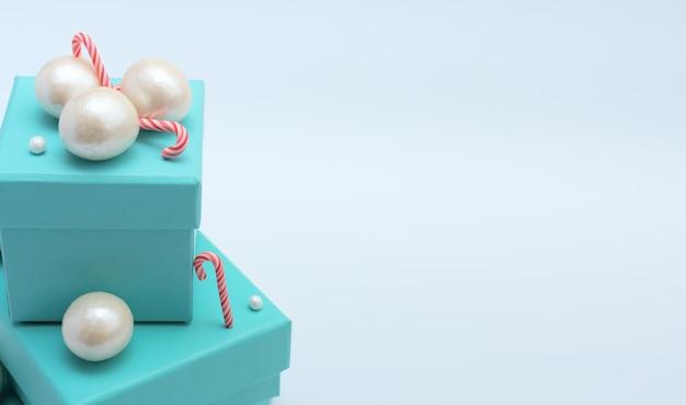 Coffrets cadeaux bleus avec des cannes de noël, grandes et petites perles sur blanc