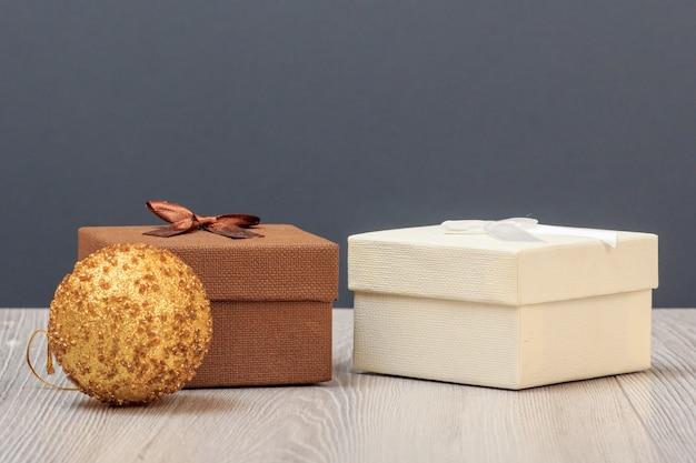 Coffrets cadeaux et boule étincelante sur planches de bois et fond gris.. concept de jour de célébration.