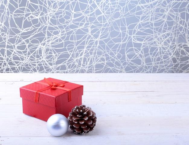 Coffrets cadeaux avec des boules de noël et arc sur fond de bois