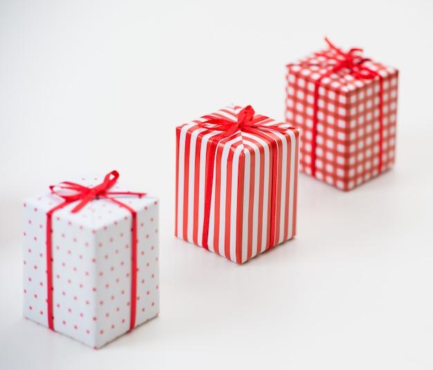 Coffrets cadeaux avec des cadeaux de noël enveloppés dans du papier rouge avec ornement sur fond blanc