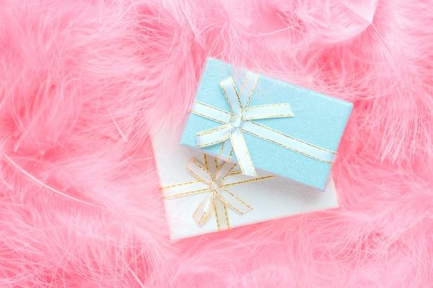 Coffrets cadeaux colorés sur fond rose pastel en plumes.