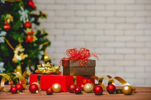 Coffrets cadeaux colorés avec noeud papillon en ruban de couleur vive placé sur le coin d'une table en bois devant un magnifique sapin de noël entièrement décoratif et un mur de briques en arrière-plan flou.