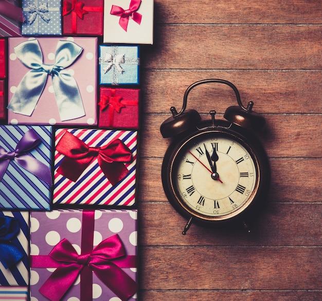 Coffrets cadeaux de couleur différente et réveil sur bois